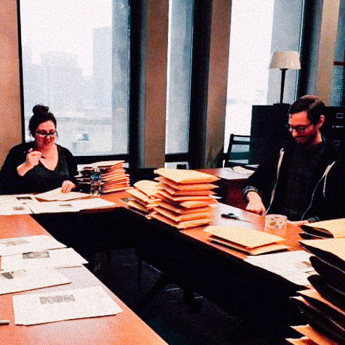 Image of a woman and man looking over pages amongst piles of folders