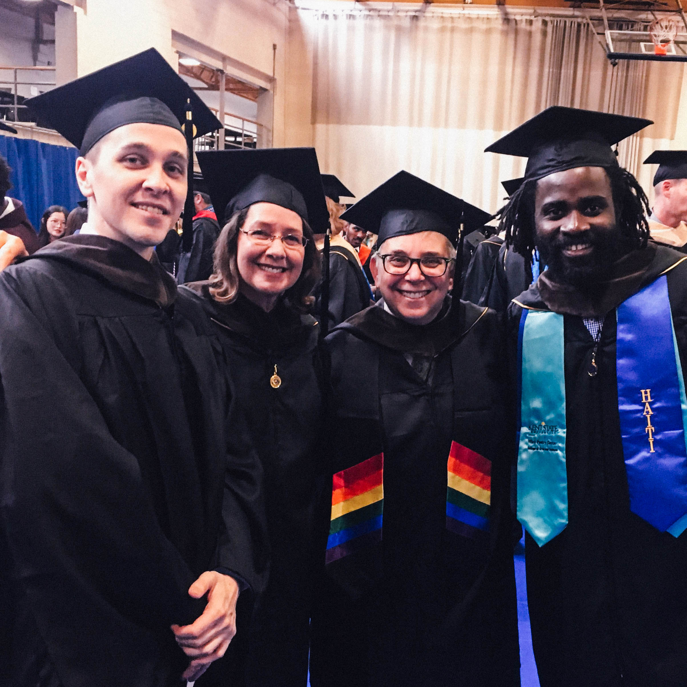 Students and professors pose together at graduation