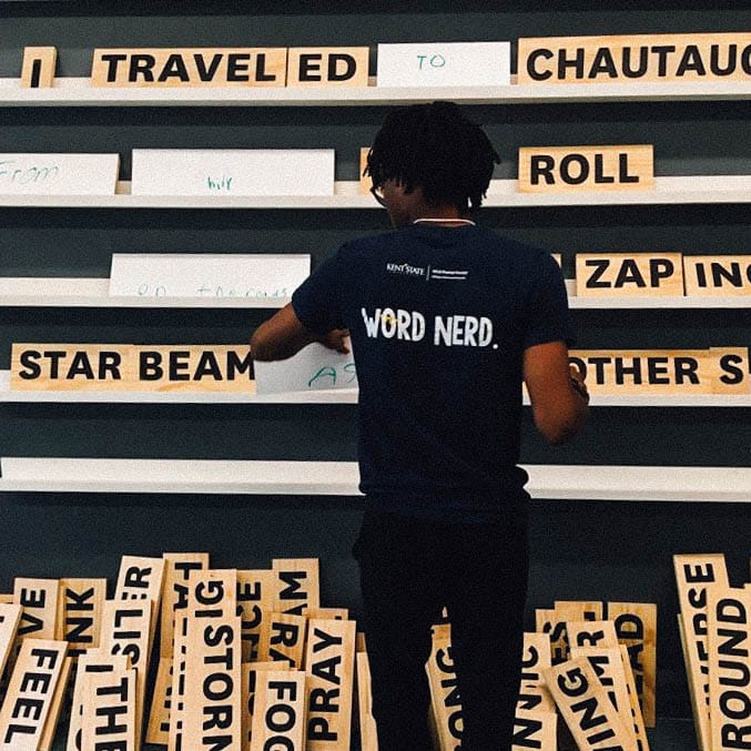 Image of a student in front of a large interchangable word wall